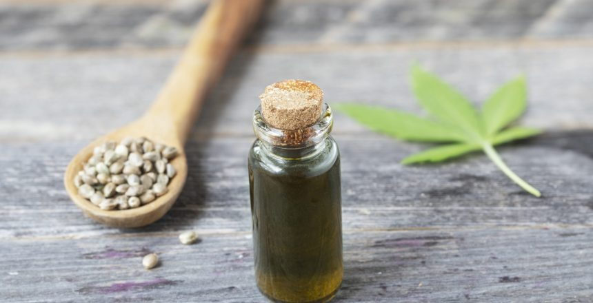 Small bottle of CBD oil with cannabis leaf and seeds in a wooden spoon.
